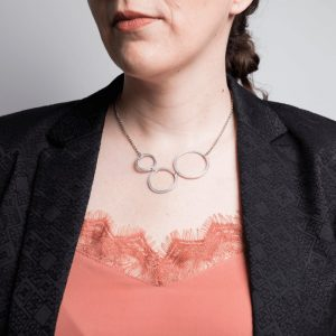 gros plan sur décolleté de femme portant un collier composé de trois ronds asymétriques en aluminium brut.